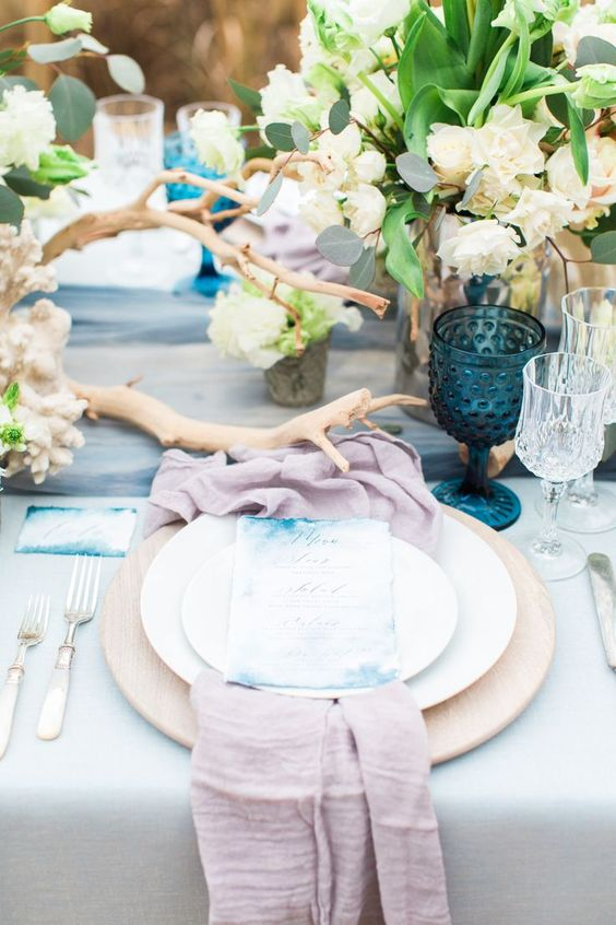 a seaside wedding tablescape with a dusty pink napkin, a blue runner, watercolor cards, deep blue glasses, white floral centerpieces and driftwood