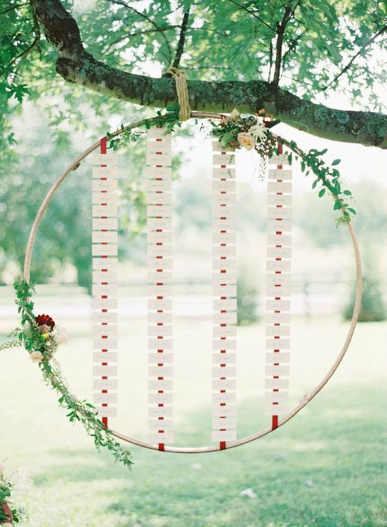 a seating chart made of an oversized embroidery hoop with lots of cards, blooms and greenery is very creative
