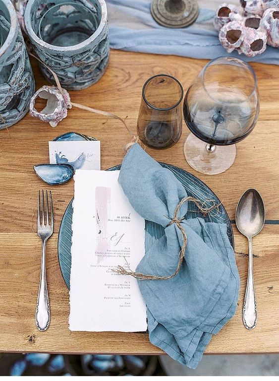 a slate blue tablescape with catchy vases, plates and napkins, seashells and watercolro cards looks very modern and stylish