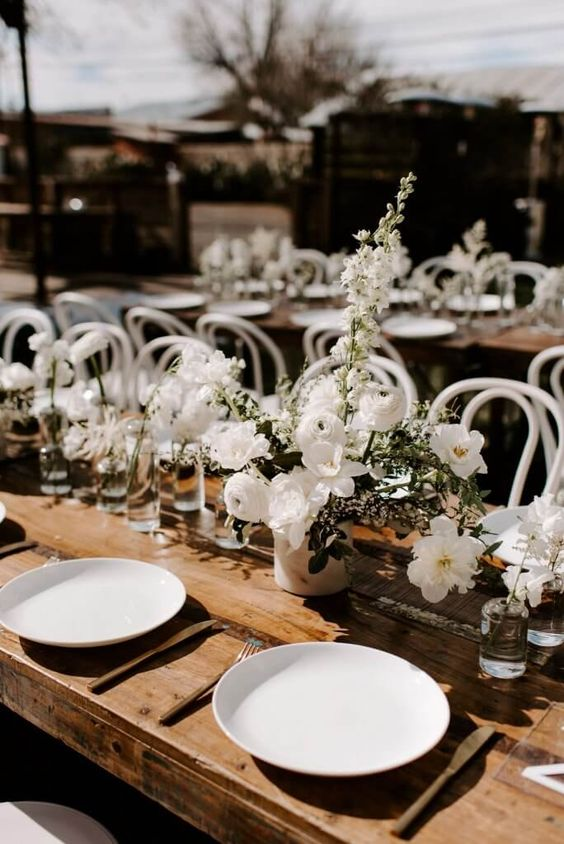 a stylish summer farmhouse wedding table with uncovered tables, white blooms and white porcelain