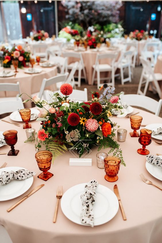 a stylish summer wedding tablescape with a bright floral centerpiece, printed napkins, colored glasses