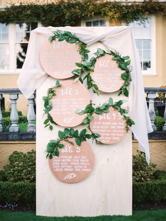a stylish wedding seating chart made of plywood circles and greenery is a stylish and chic idea