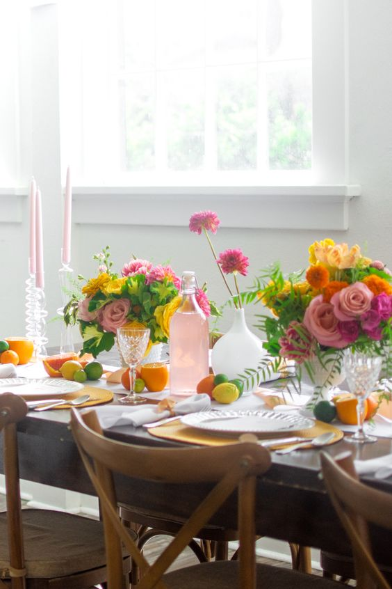 a super bright summer citrus tablescape with bold blooms, pink candles, yellow chargers and citrus right on the table