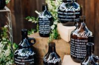 a super creative wedding seatign chart composed of large glass bottles is a cool idea for a vineyard wedding