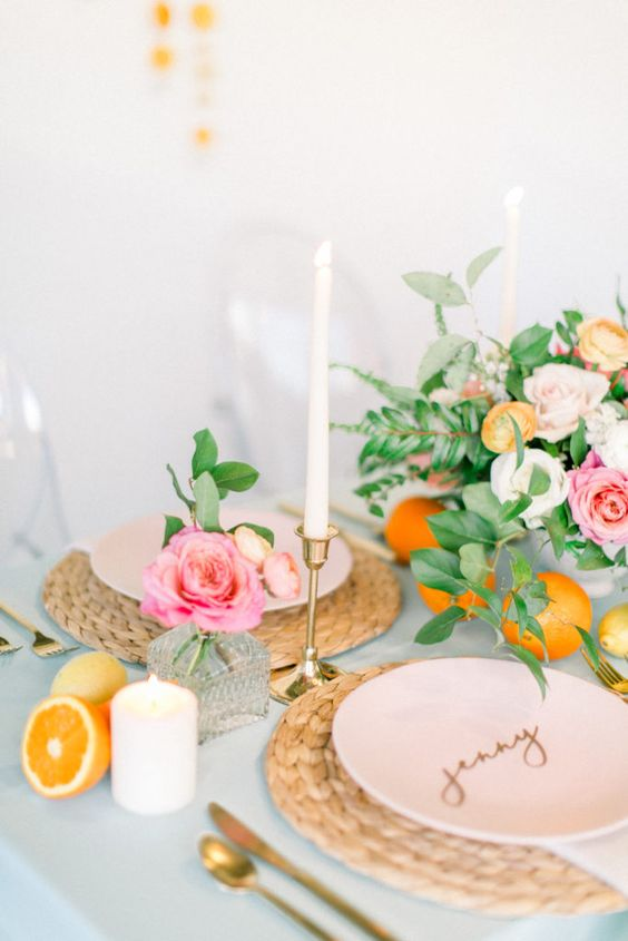 a tender summer wedding tablescape with citrus, white candles, bright blooms, woven placemats and gold touches