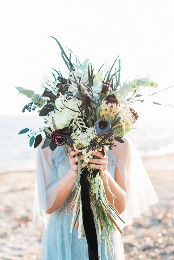 a textural beach wedding bouquet done in white, grey and pale blue, with lots of greenery and grasse