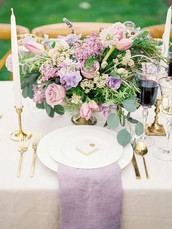 a textural lilac napkin and a lilac and blush wedding centerpiece with some foliage for a beautiful garden wedding
