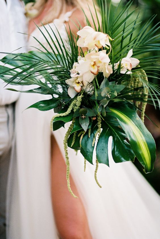 a tropical beach wedding bouquet with large tropical leaves and greenery plus neutral blooms
