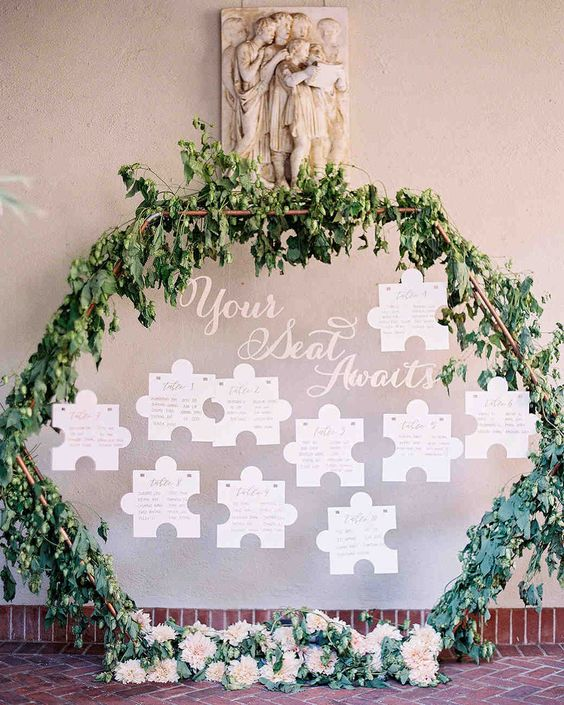 a unique wedding seating chart with lush greenery, blush blooms and a puzzle piece plan