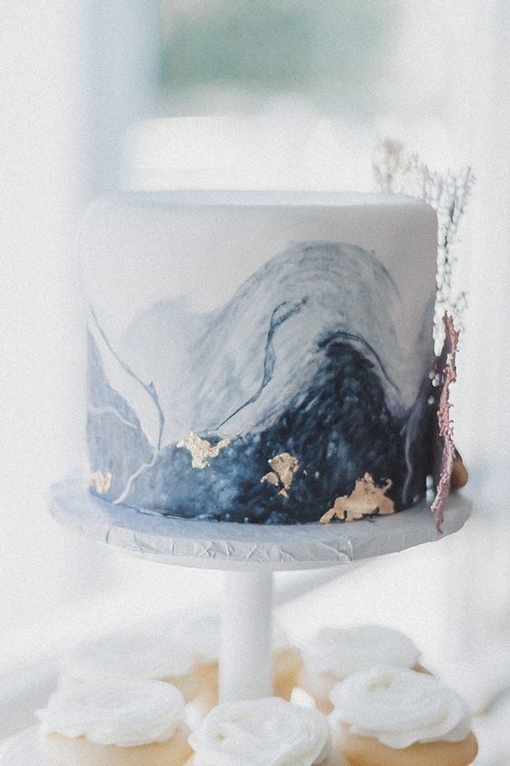 a watercolor blue and navy wedding cake with gold leaf and coral detailing is a stylish dessert for a modern coastal wedding
