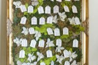 a wedding seating chart with moss, greenery, white blooms and tags is a whimsical idea