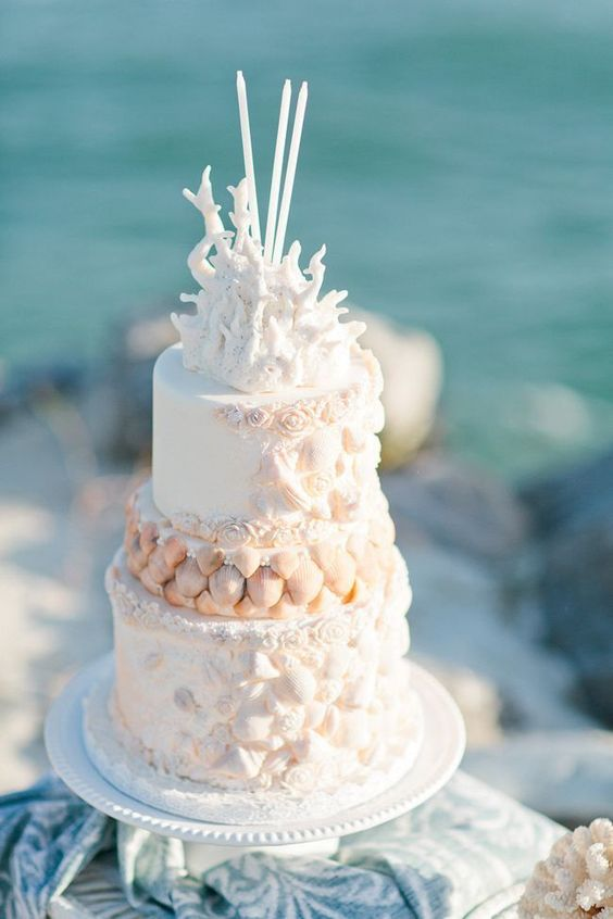 a whimsical white beach wedding cake decorated with sugar seashells, roses and corals and some thin candles on top