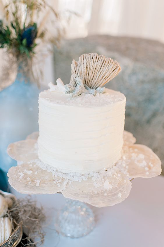 a white beach wedding cake topped with corals and shells plus sea salt mad eof sugar is a lovely idea