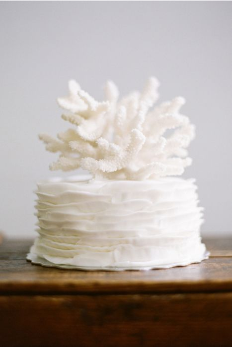 a white ruffle wedding cake with a large coral on top feels very coastal and beachy and looks very elegant