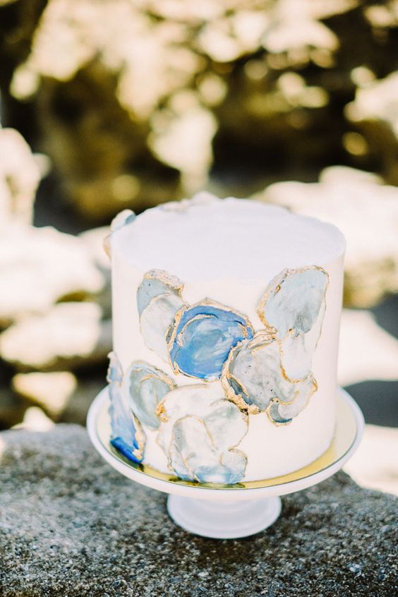 a white wedding cake decorated with blue and grey geode slices with a gold edge is a lovely and chic coastal idea