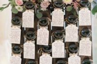 a winery wedding seating chart with bottles and bright blooms and greenery is a chic idea