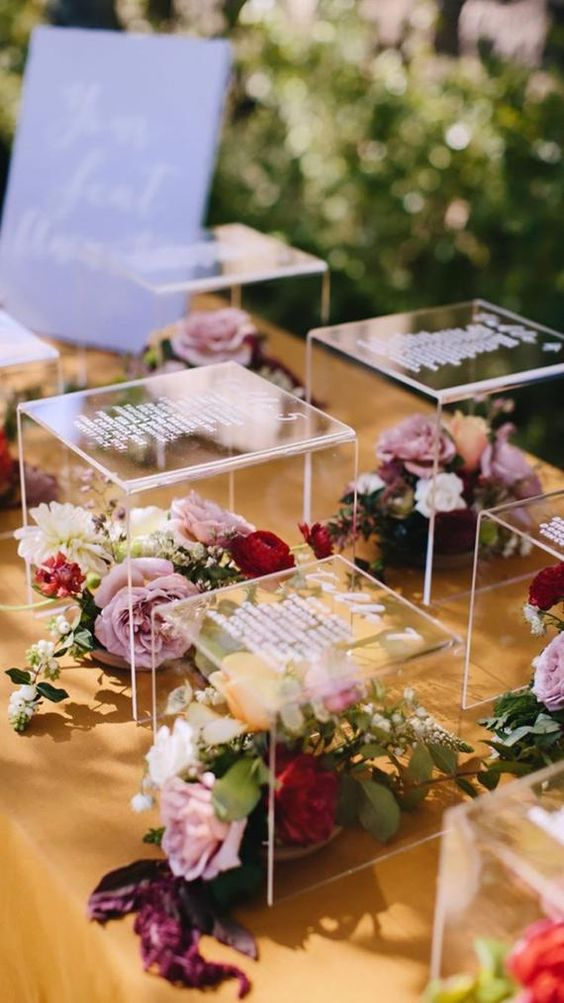 an acrylic riser seating chart with bright blooms and greenery is a chic and stylish idea for a modern wedding
