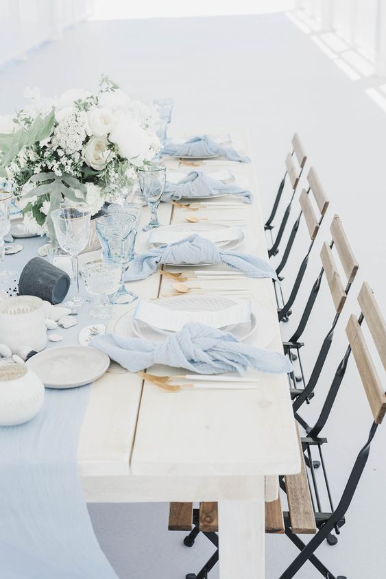 an ethereal light blue wedding table with a fabric runner and matching napkins, gilded cutlery, pebbles and neutral blooms