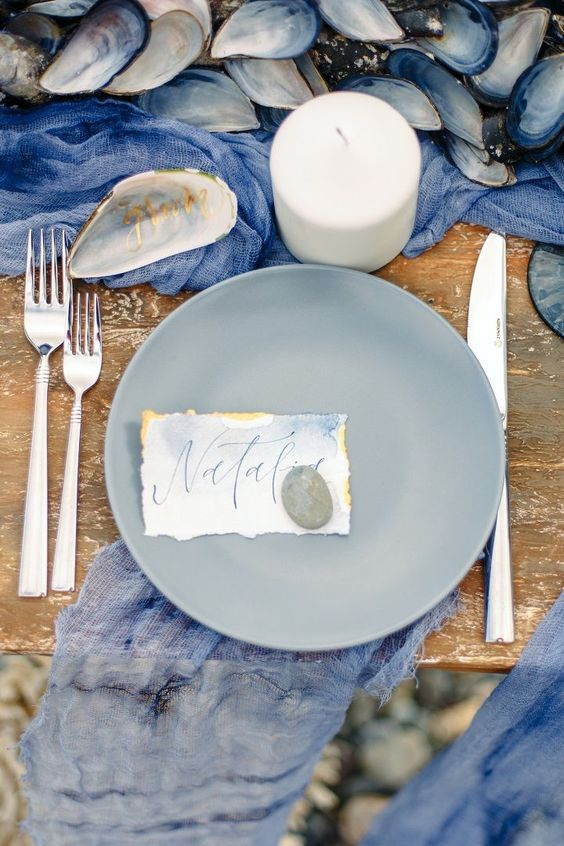 an oceanside wedding tablescape with a deep blue runner and napkins, grey porcelain, candles, seashells, watercolor cards