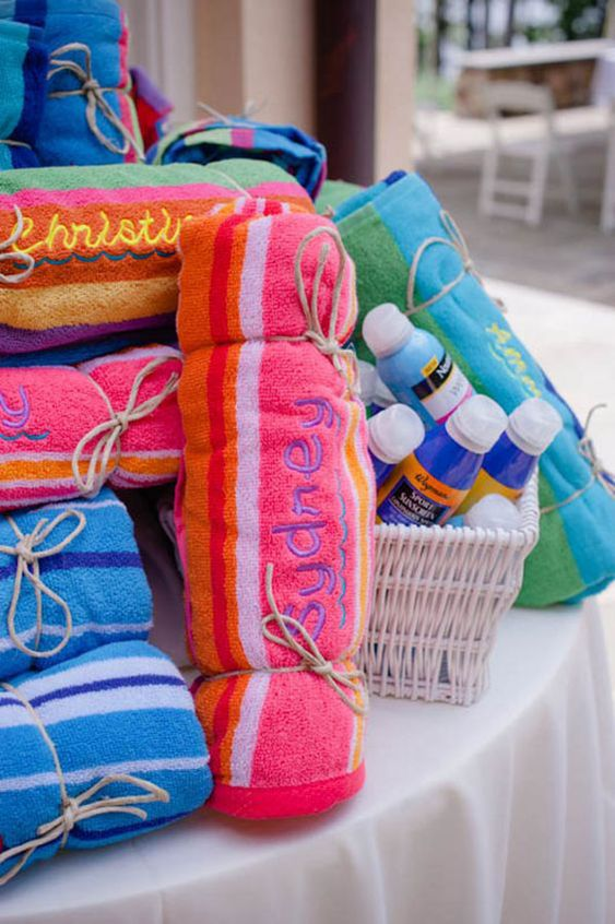colorful embroidered towels and sunscreen are perfectly useful beach wedding favors to give to your guests