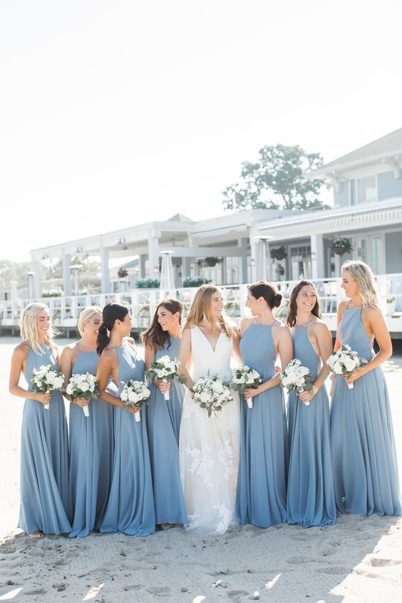 matching blue maxi bridesmaid dresses with halter necklines and pleated skirts for a bright beach wedding