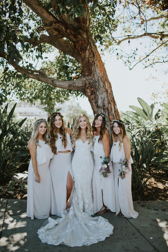 matching white bridesmaid separates with halter neckline crop tops and maxi skirts with slits for a modern beach wedding