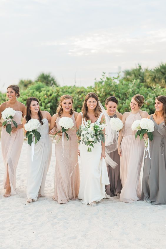 mismatching blush, white and taupe maxi bridesmaid dresses with draped bodices and skirts for a cool beach wedding