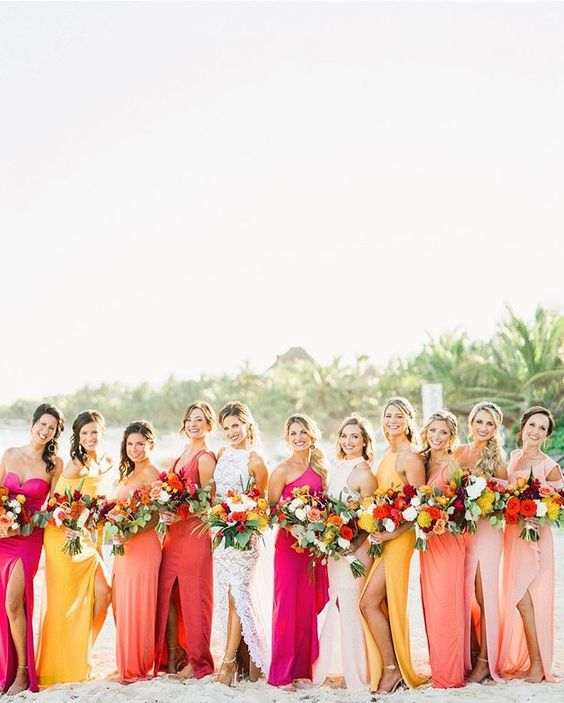mismatching coral, blush, yellow and hot pink maxi bridesmaid dresses with various slits are bold and cool