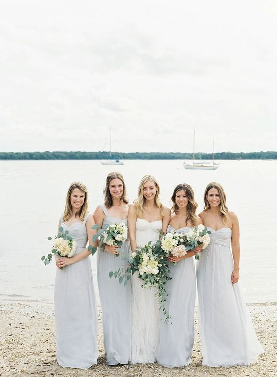 mismatching pale blue maxi bridesmaid dresses with draped bodices and pleated skirts for a pastel beach wedding