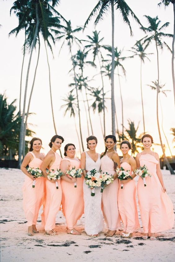 mismatching peachy pink maxi bridesmaid dresses for a bright and cheerful tropical beach wedding