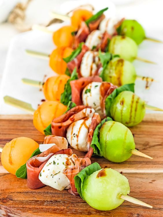 prosciutto, melon and mozzarella skewers with greenery and herbs are a timeless appetizer for a tropical wedding