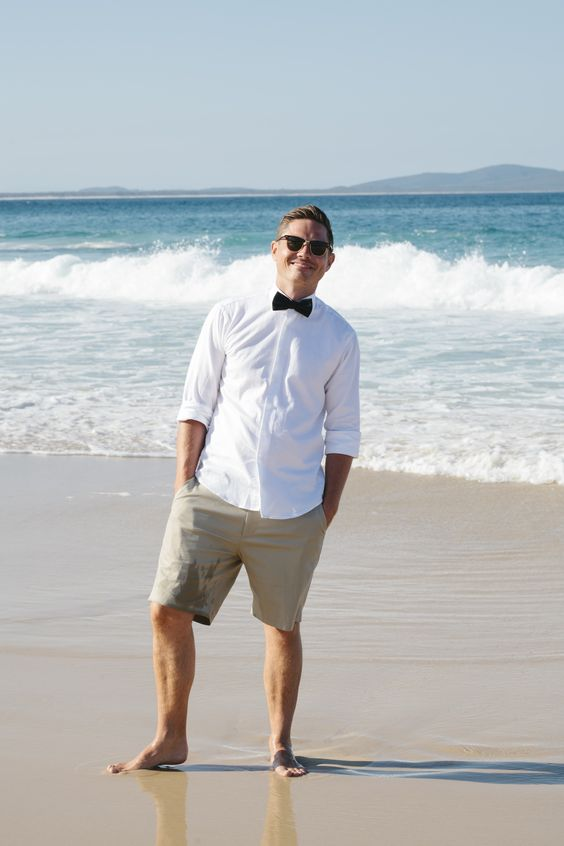 tan shorts, a white shirt, a black bow tie and stylish sunglasses for a relaxed and comfy look