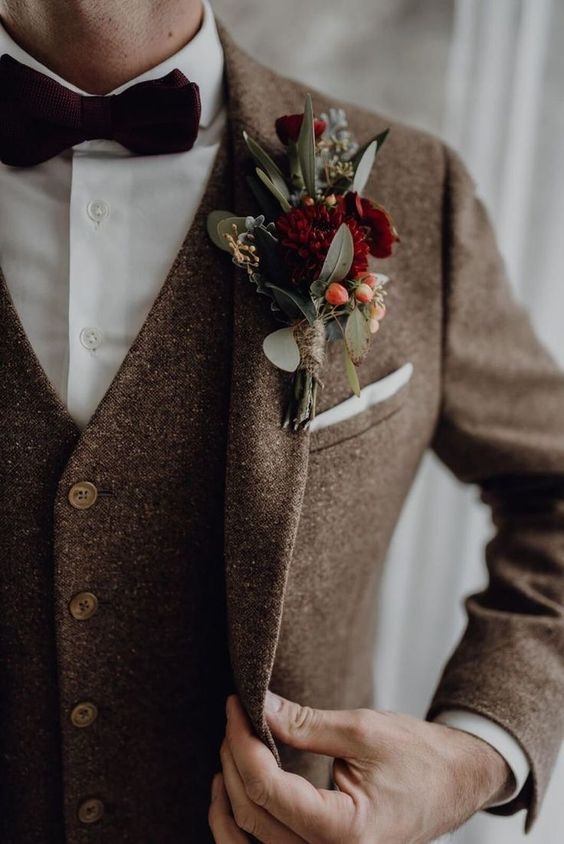 a chic brown tweed three-piece suit, a whiet shirt, a burgundy velvet bow tie and a floral boutonniere