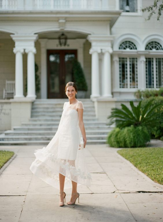 a chic white mini dress with a sheer lace applique overdress, metallic shoes and statement earrings