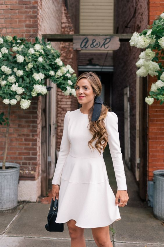 a chic white over the knee dress with a high neckline, long sleeves and a black bow in the hair make up a cool look
