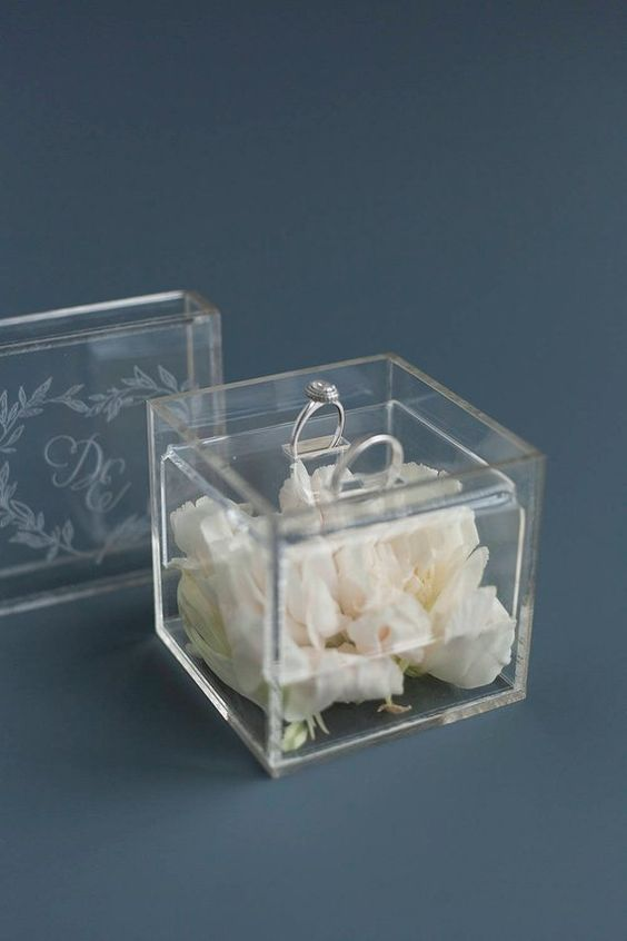 a clear acrylic box filled with white blooms is a cool idea for a modern or minimalist wedding