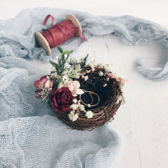 a faux bird nest decorated with fresh blooms and greenery is a very cozy and cute idea for a woodland or backyard wedding