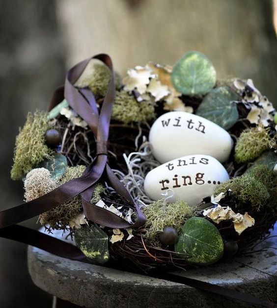 a faux bird nest with moss, foliage and berries plus fake eggs with letters for a fall or spring woodland wedding