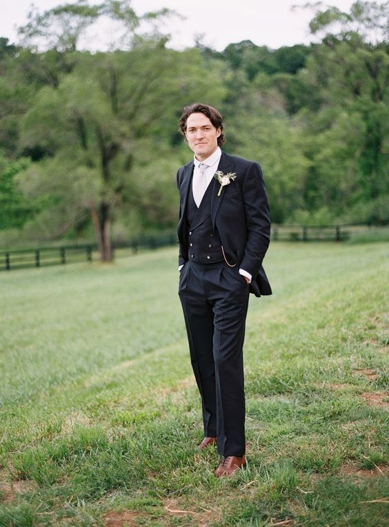 a formal vintage three-piece groom's suit with a white shirt, a neutral tie, brown shoes and a floral boutonniere
