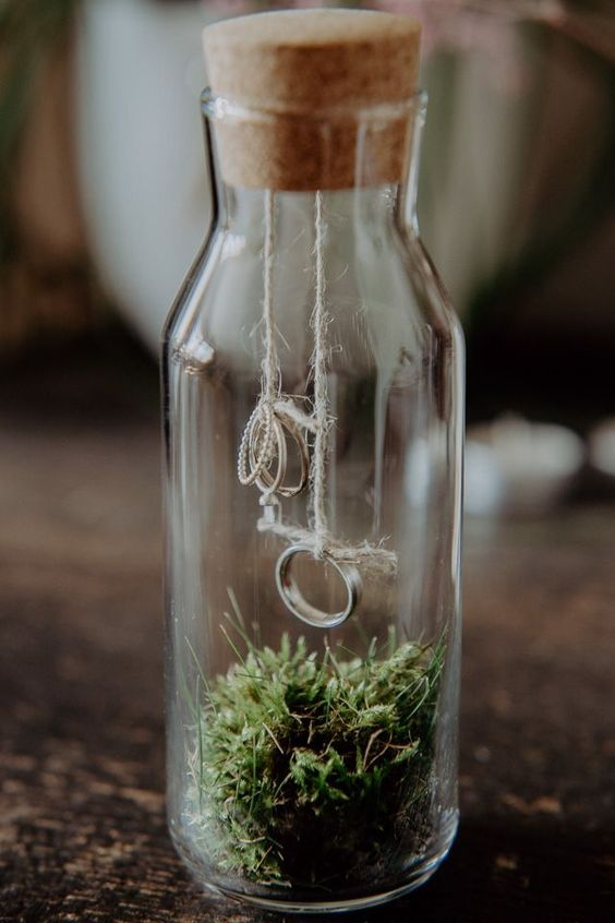 a glass bottle filled with moss and with rings attached to the cork is a cool woodland wedding idea