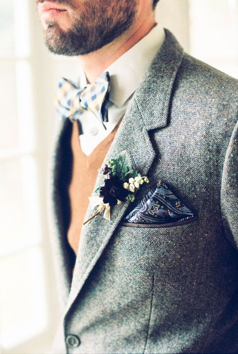 a grey tweed suit, a tan waistcoat, a neutrla button down, a printed bow tie and handkerchief