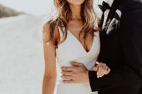 a minimalist sheath wedding dress with a deep neckline and a train is a cool option to wear right now