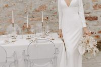 a minimalist sheath wedding dress with a plunging neckline, long sleeves, a train for a refined modern bride