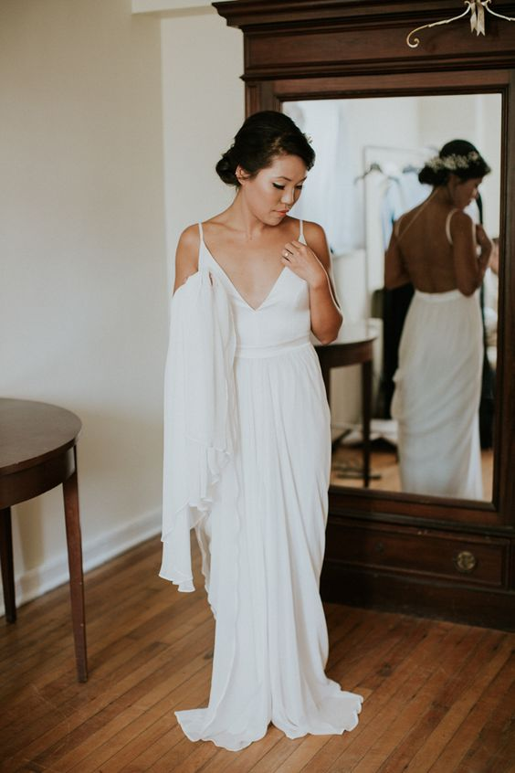 a minimalist sheath wedding dress with a sleek plain bodice and a draped skirt with a small train plus spaghetti straps