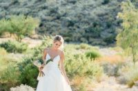 a minimalist wedding ballgown with a plunging neckline, spaghetti straps and a train for a modern romantic bride