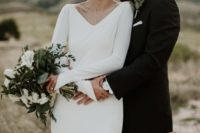 a modern A-line wedding dress with a V-neckline and long bell sleeves plus an open back