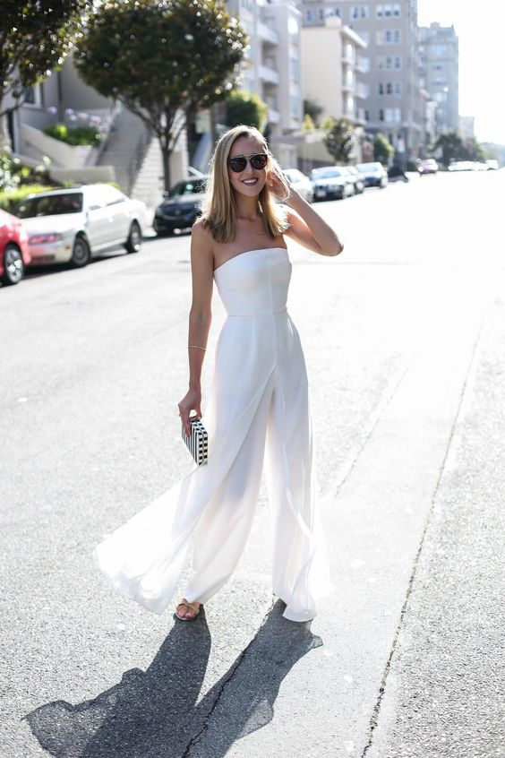 a modern strapless fitting jumpsuit and an overskirt, metallic heels and a striped clutch