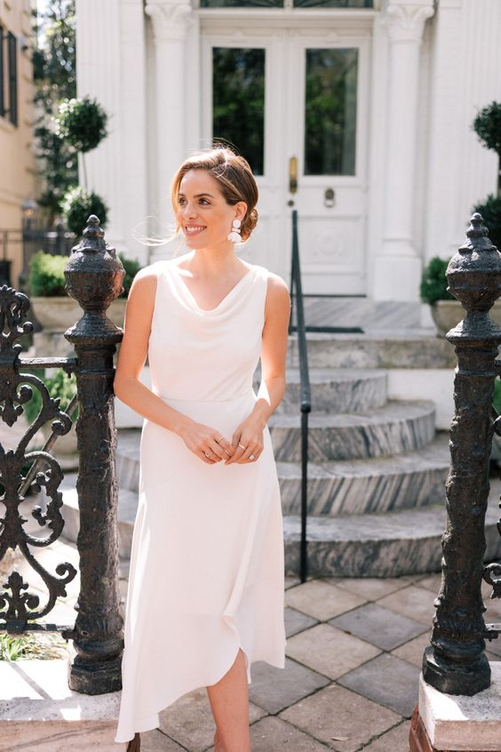 a modern white midi dress with a cowl neckline, no sleeves and an asymmetric skirt plus statement earrings