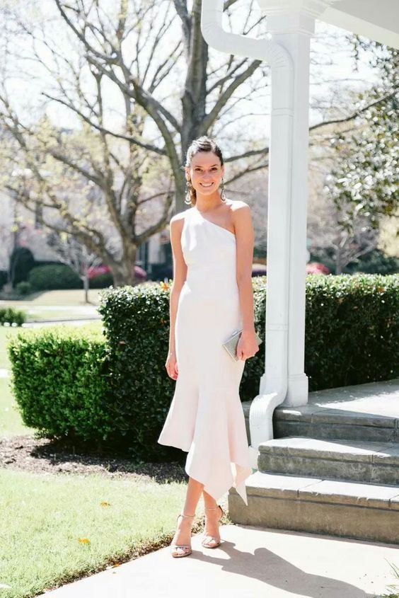 a one shoulder sheath white dress with a ruffled asymmetrical skirt, statement earrings and shoes