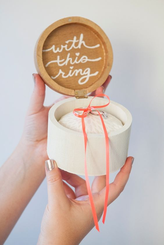 a round wooden box with calligraphy and your rings in it is a cool idea for a modern or cozy casual wedding